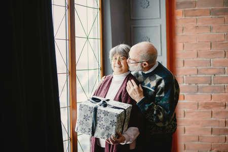 An elegant old couple are celebrating Christmas Zdjęcie Seryjne - 159595568