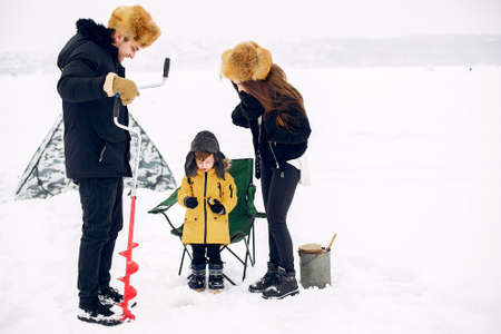 Cute family sitting on a winter fishing with little son
