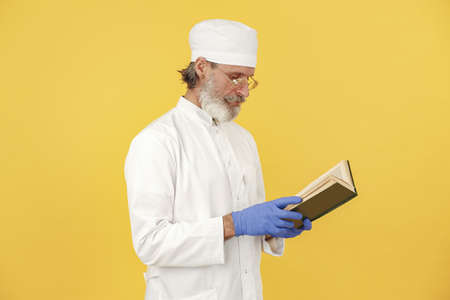 Old doctor standing in a white uniform