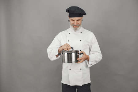 Chef in white uniform over gray background