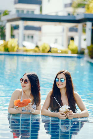 two girls having fruit by the pool