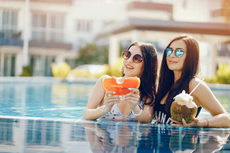 two girls tanning and having fruit by the pool Zdjęcie Seryjne
