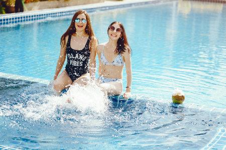 two girls having fun by the pool Zdjęcie Seryjne