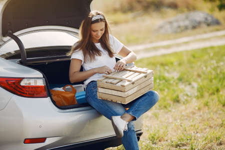 Elegant woman sitting in a trunk with wood box