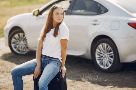 Elegant woman by the car with a suitcase
