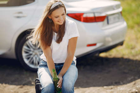 Elegant woman standing by the car