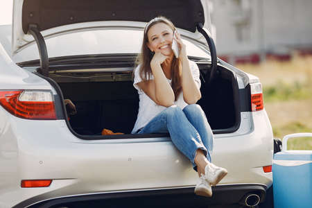 Elegant woman sitting in a trunk with mobile phone