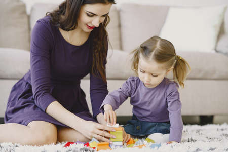 Cheerful mom playing laughing with little kid daughter
