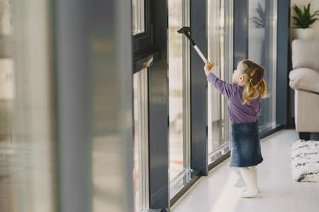 Little girl cleaning windows with vacuum cleaner