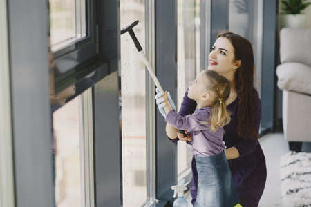 Daughter and mother cleaning window together Zdjęcie Seryjne