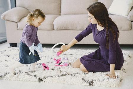 Little girl cleaning floor with toy vacuum cleaner Zdjęcie Seryjne