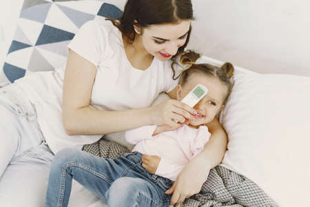 Mother with thermometer is sitting near daughter