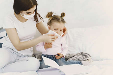 Mother and baby at home with medical masks