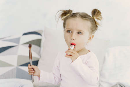 Pretty little girl with makeup cosmetics at home