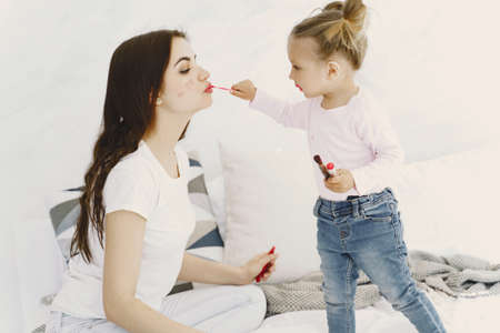 Mom playing with cosmetics in bed with her daughter Zdjęcie Seryjne