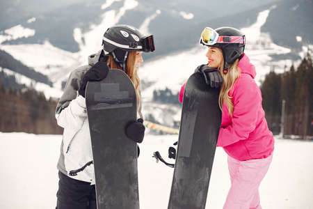 Girls snowboarding in the mountains with the snowboard