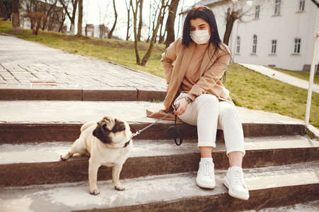Brunette in a mask walks with pug