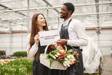 Flower sellers with a sign and with tulips Imagens