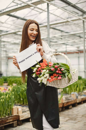 Girl with a basket of tulips in greenhouse.