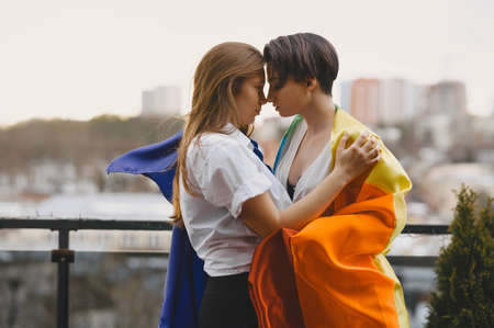 Lesbians hug and love each other with LGBT flag Imagens