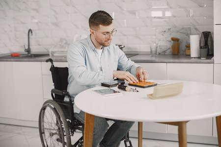 Young disabled man repairing motherboard at kitchen Stock Photo