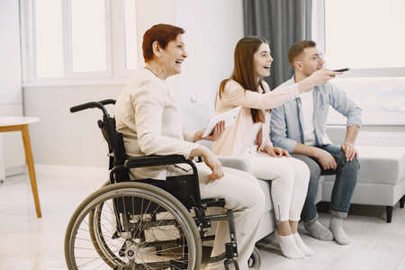 Woman in wheelchair watch tv with caregivers