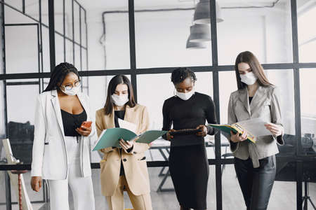 The business women wearing masks while working at office