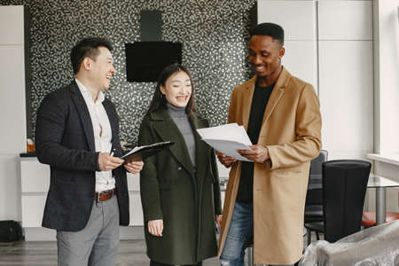 Realtor Explaining Agreement To Couple In New Apartment Banque d'images