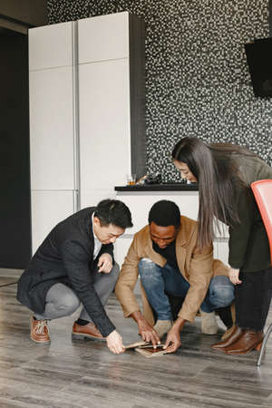Couple discussing with designer or rieltor apartment project Banque d'images