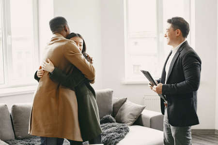 Asian wife and black man hugging in their flat Banque d'images