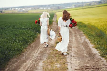 Women in elegant dress standing in a summer field Zdjęcie Seryjne