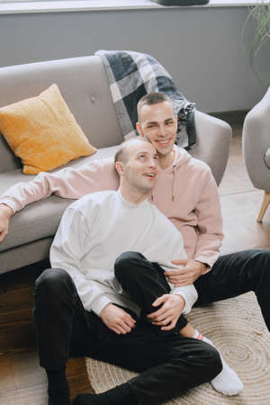 Delighted gay couple watching television together at home