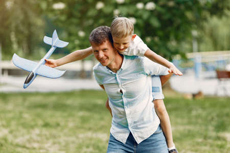 Father with little son playing with toy plane