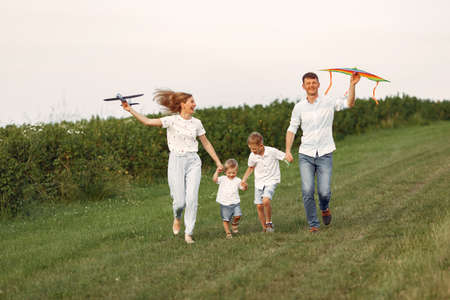 Family walks in a field and playing with toy plane