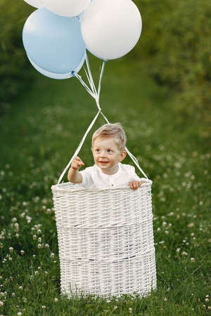 Little child sitting in the basket with balloons
