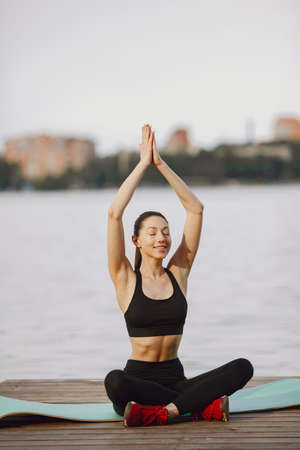 Woman practicing advanced yoga by the water