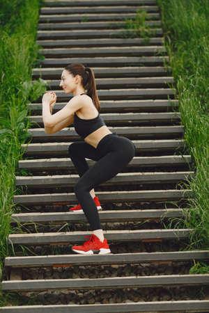 Woman in a black spoerswear standing on a stairs