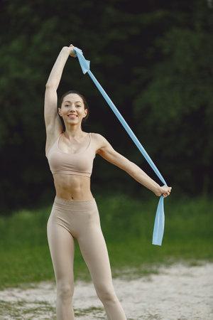 Woman practicing advanced yoga on a summer beach