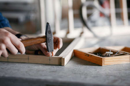 Carpenter hammering a nail in a workshop