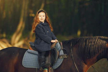 Cute little girl in a autumn field with horse 版權商用圖片