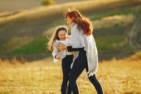 Mother with little daughter playing in a autumn field 版權商用圖片