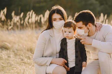 Stylish family in a masks walking on a spring field 版權商用圖片