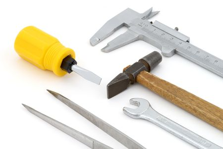 pincers: Tools on background. Chrome wrench, vernier calipers, pincers, hammer and screwdriver with yellow plastic handle
