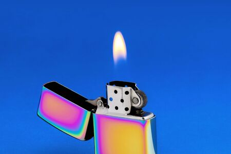 Golden metal cigarette lighter with flame on blue background. Selective focus photo