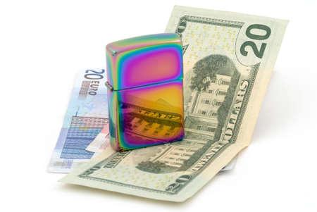 Golden metal cigarette lighter.  Euro and dollar banknotes. Selective focus photo