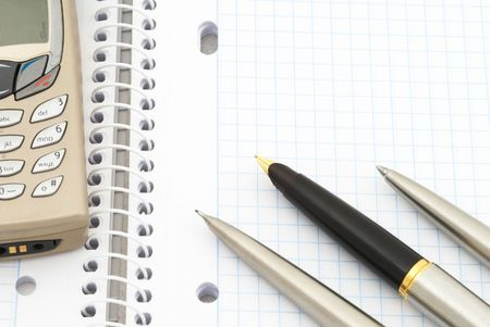 Business background. Mobile telephone and spiral notebook with blue grid. Selective focus photo