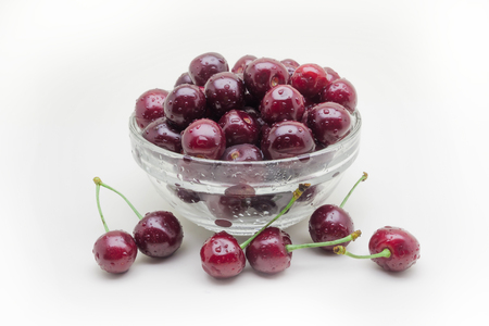 Glass vase with crumbling cherries isolated on white background