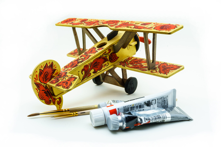 Toy airplane painted in khokhloma style, acrylic paints and brushes on white background