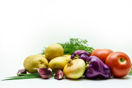 Assortment of fresh raw vegetables isolated on white background. Selection includes potato, tomato, green onion, pepper, garlic and dill