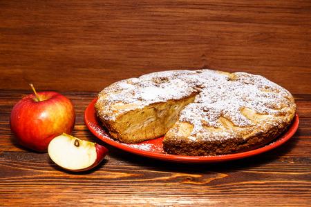 Apples and freshly baked apple pie on rustic background of dark wood.